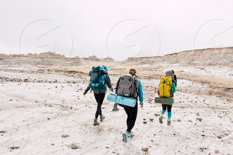 3 people with backpack and sleeping bags walking in the middle of a rocky land with beige sand during daytime photo