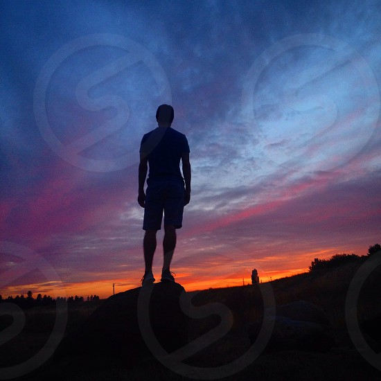 man standing on rock overlooking the sunset view photo
