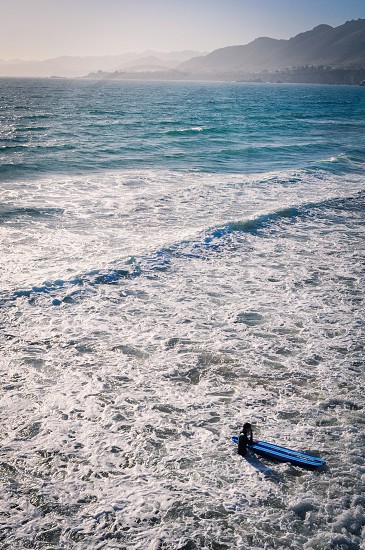 man standing near surfing board photography photo