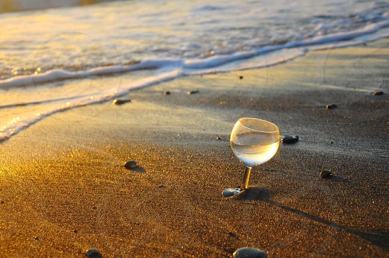 clear wine glass on beach beside shore photo