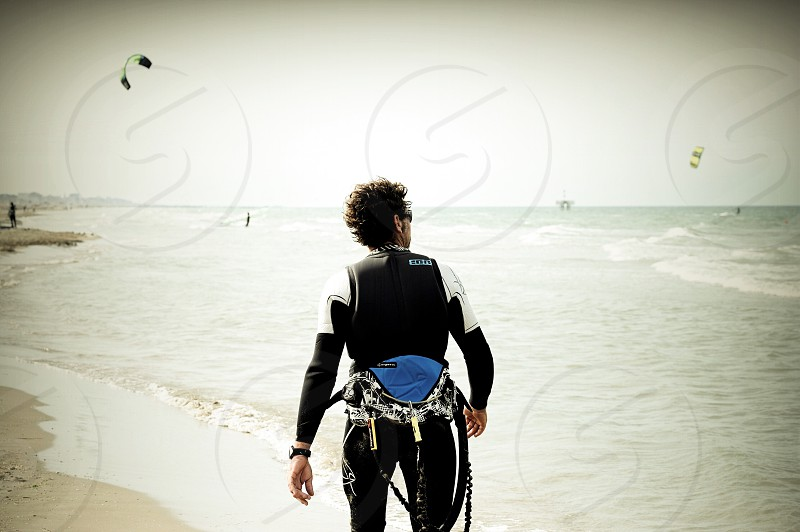 man in black and white rash guard standing by the seashore photo