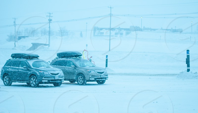 Cars parked during heavy snow storm with ski racks on top photo