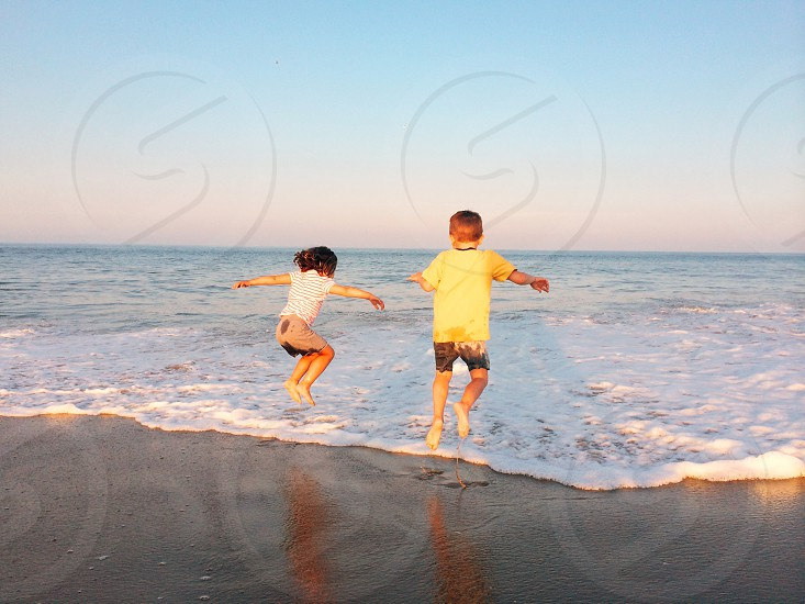 girl and boy playing on beach photo
