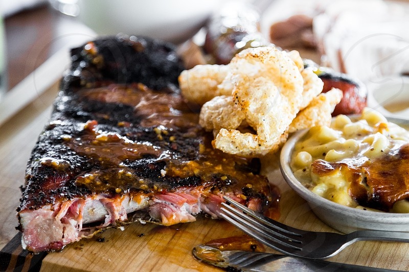 A platter of delicious BBQ with sausage ribs turkey and southern sides like collard greens pork rinds and mac and cheese. Many different sauces are available at each table. photo
