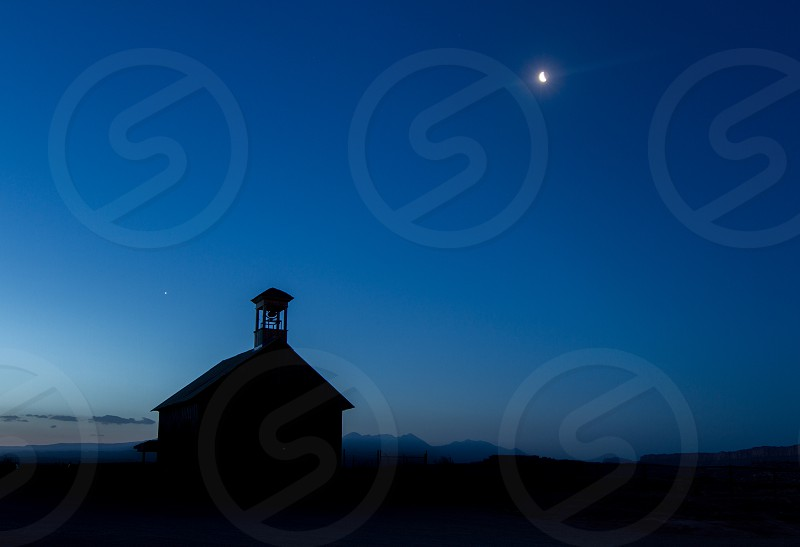 An old schoolhouse silhouetted against the night sky and moon photo