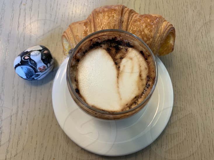 Creative breakfast with my espresso coffee with milk croissant and a funny cow stone at the bar photo