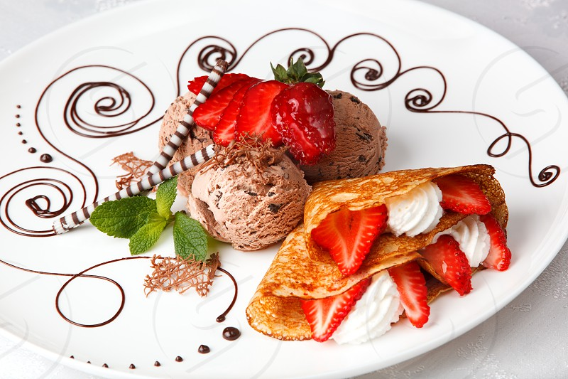 Delicious golden freshly baked strawberry and cream pancake with chocolate ice cream for a gourmet dessert photo