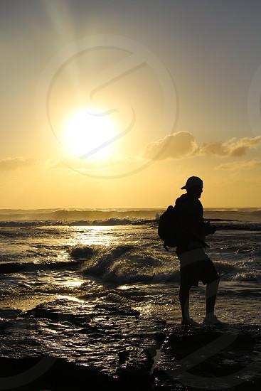 lens flare man beach waves sky hat backpack photo