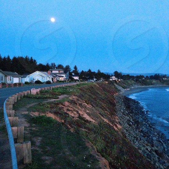 road by a cliff waters edge white homes photo