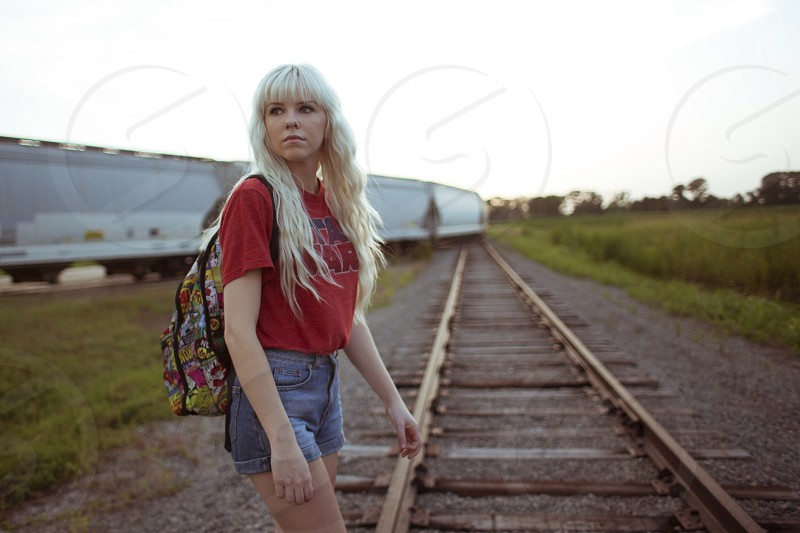 woman in red t shirt and shorts with backpack on train track photo
