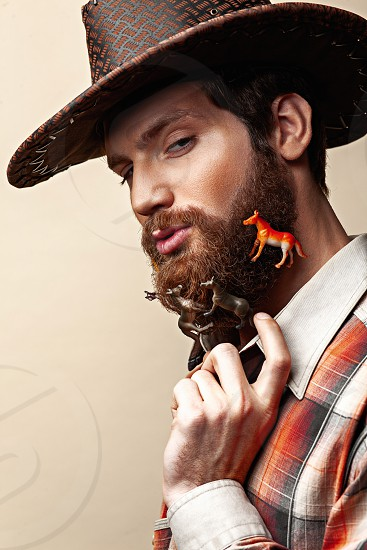 Young man in a cowboy hat and toy horses in a beard photo