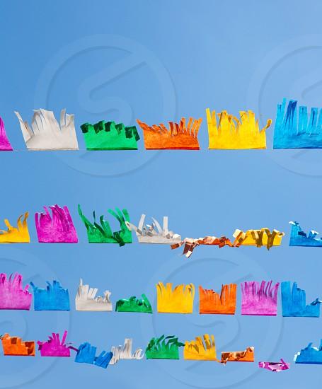 colorful tissue Paper fringe garland under blue sky in Spain fest photo