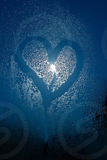Moonlight through the window. Sweaty glass and heart shape photo