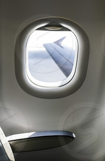 Plane interior sit and window. Airplane wing seen through the window. Air transport concept. photo