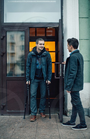 man in formal suit holding door open while man using crutches during daytime photo