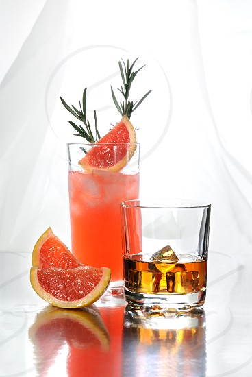 Paloma cocktail in Collins Glass from tequila with grapefruit juice decorated with a slice of grapefruit and rosemary.Whiskey in rocks glass with  ice cubes . Drinks  on a light background. photo