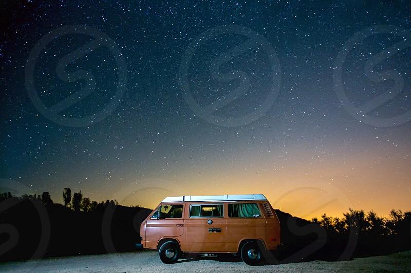 brown van beside bare trees during nighttime photo