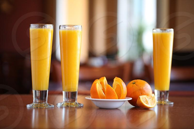Three 3 tall glasses of orange juice and slices. Yellow restaurant drinks breakfast photo