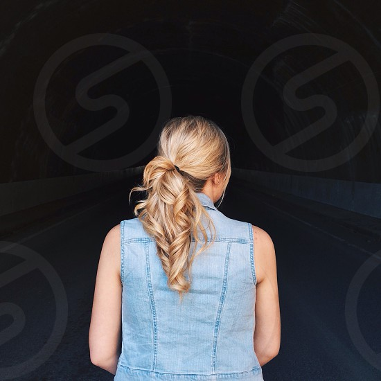 woman in blonde ponytail with bleached denim vest photo