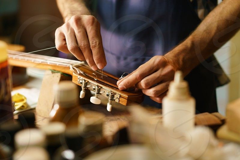 guitar; artisan; lute; maker; luter; string; lutemaker; man; fixing; cord; palette; acoustic; music; broken; shop; caucasian; classical; classical guitar; apron; crafts; dedication; examining; expertise; handmade; inspecting; luter shop; making; one person; people; person; precision; preparing; profession; professional; restoration; skilled; small business; string instrument; studio; talleur; uniform; wood; wooden; work; working; young adult photo