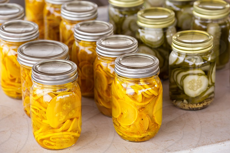 Pint jars of preserved squash and cucumbers  photo