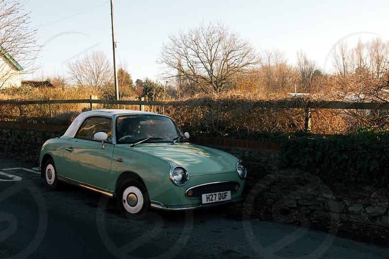 A classic Nissan Figaro basks in the sunshine on a beautiful winter's day. Taken in Lympstone Devon UK. photo