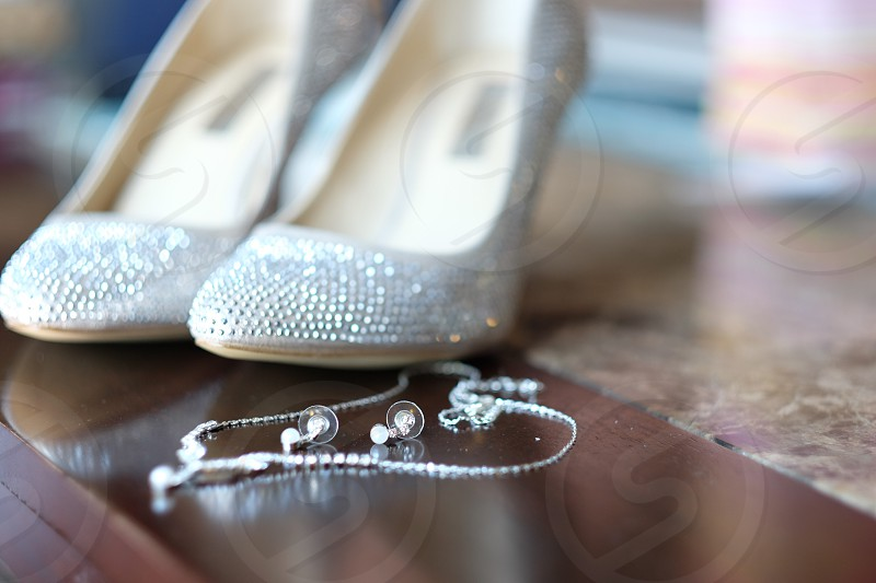 grey glitter stilettos near silver chain necklace and silver stud earrings photo