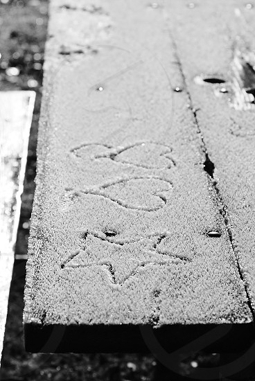 snow covered plank with hearts and star drawing photo