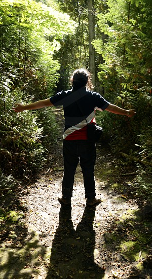 Freedom inspirational dramatic sunlight silhouette of man with wide open arms in the green forest photo