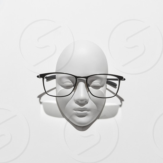 Elegant glasses on a gypsum face sculpture with shadows on a white background copy space. Glasses for reading and person with visual impairment. Top view. photo