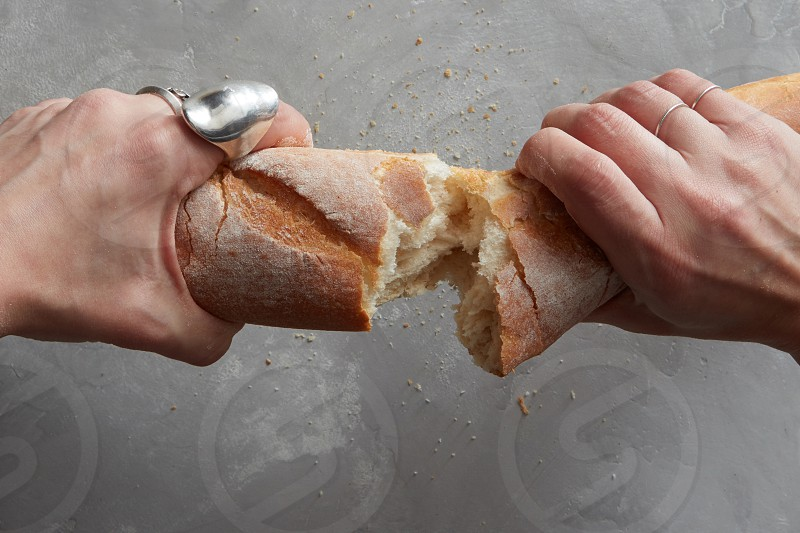 female hands breaking freshly baked bread on a gray stone background photo