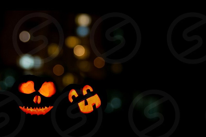 Two lit jack-o-lanterns on Halloween night. photo