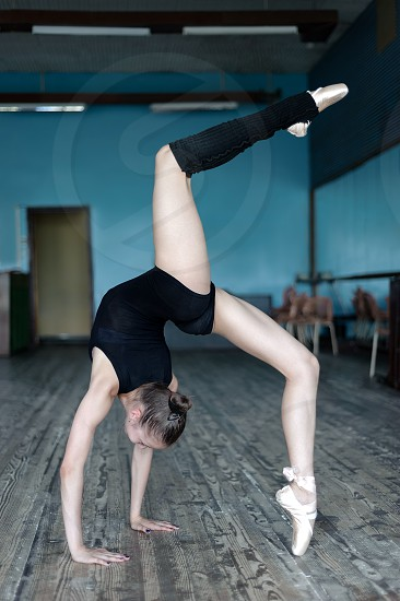 Young graceful ballerina practising in the studio standing in position on hands photo