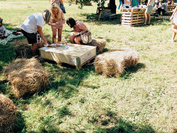 women sitting on hay bales around a table un the sun photo