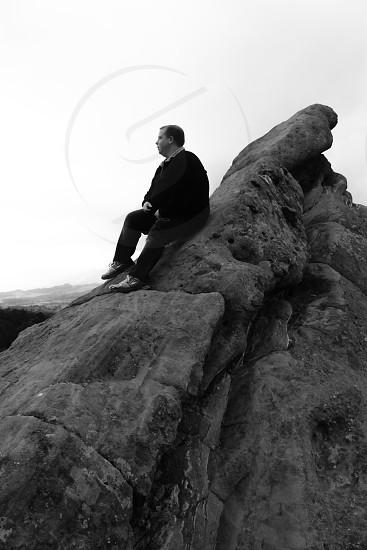 woman wearing black sweater on top of rock photo