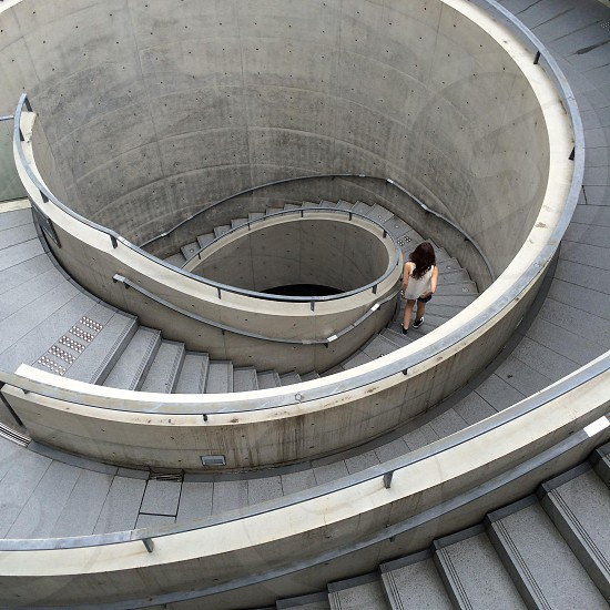 woman walking down on gray spiral staircase photo