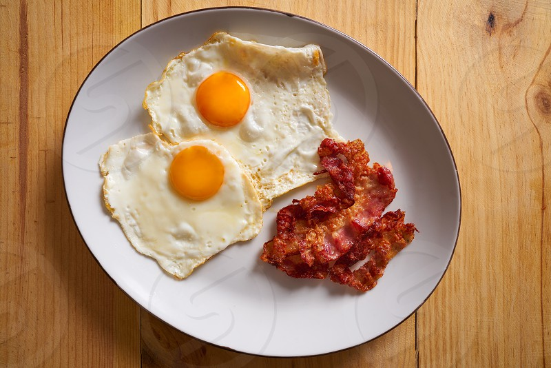 Breakfast bacon and eggs over easy on wood table photo