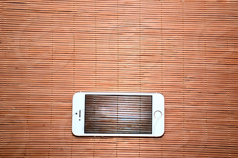 gold iphone 5s on brown wooden surface photo