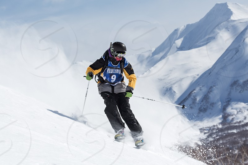 KAMCHATKA PENINSULA RUSSIAN FAR EAST - MARCH 9 2014: Skier rides steep mountains. Competitions freeride snowboarders and skiers Kamchatka Freeride Open Cup. Russia Far East Kamchatka Peninsula. photo