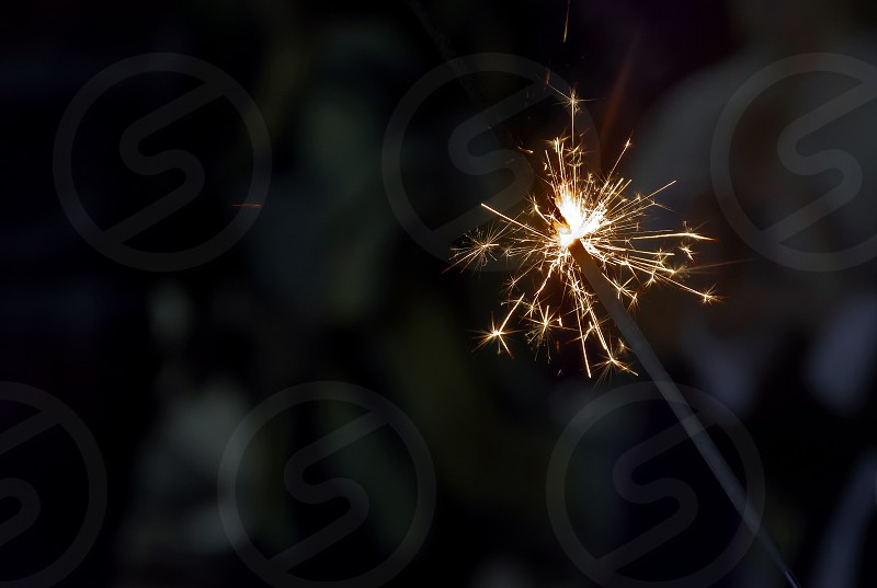 Glowing holiday sparkling hand fireworks shining fire flame photo