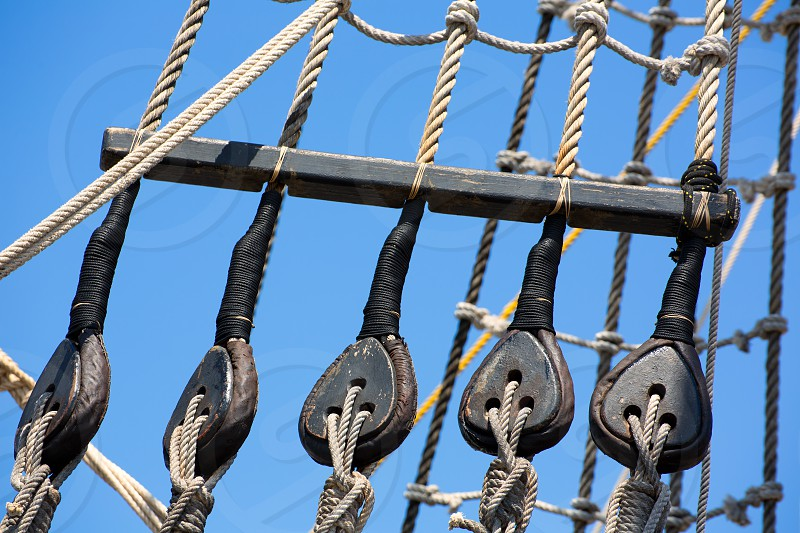 Vintage wooden boat pulley and ropes detail under blue sky photo