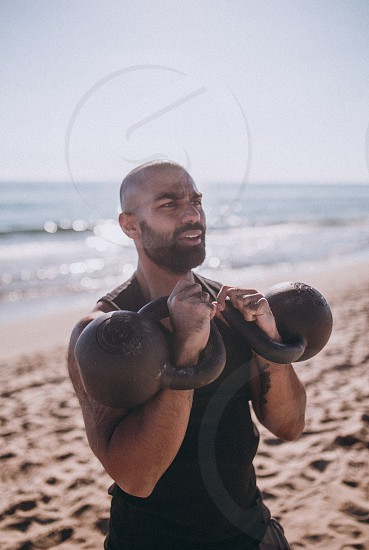 Young man is liftig heavy kettle balls for his tough workout exercise photo