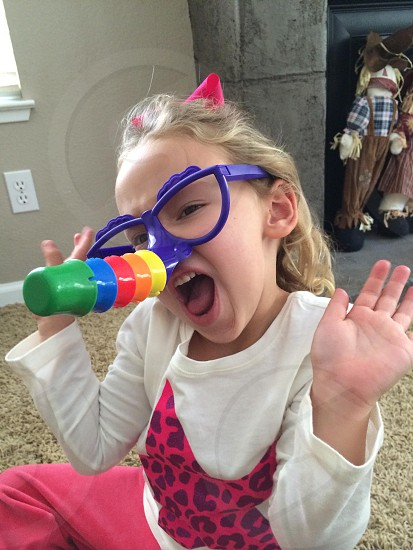 girl in blue glasses making face photo