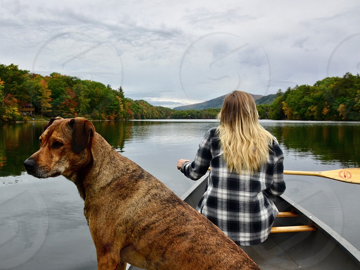 medium short-coated black brindle dog on gray boat with woman in white and black checked dress shirt holding paddle photo