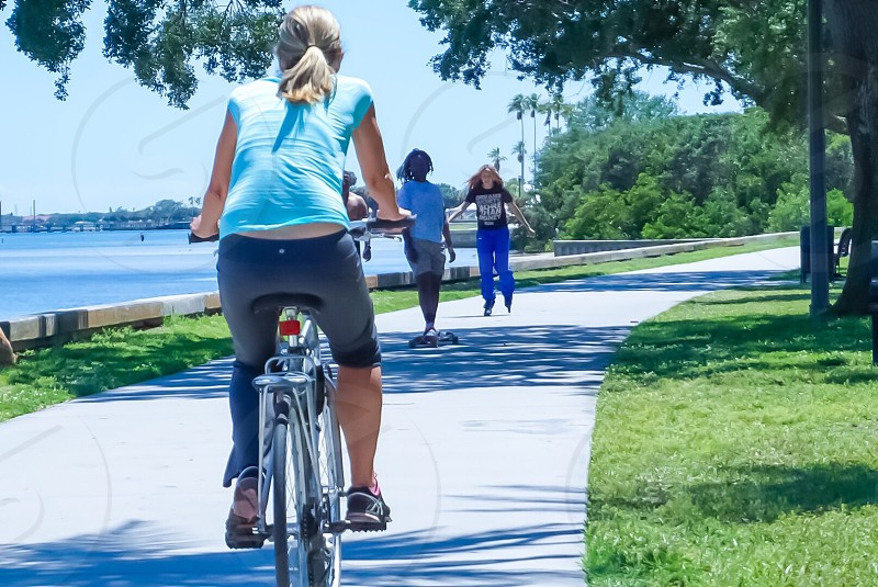 Fun summer break path. Waterfront water bay biking skateboarding rollerblading park exercising getting fit physical exercise summertime  photo