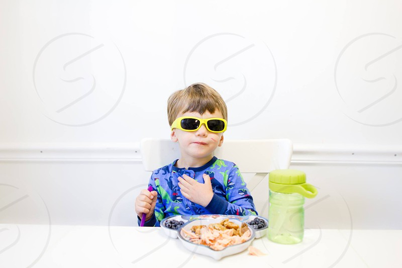 boy in blue long sleeve shirt with yellow framed sunglasses eating photo
