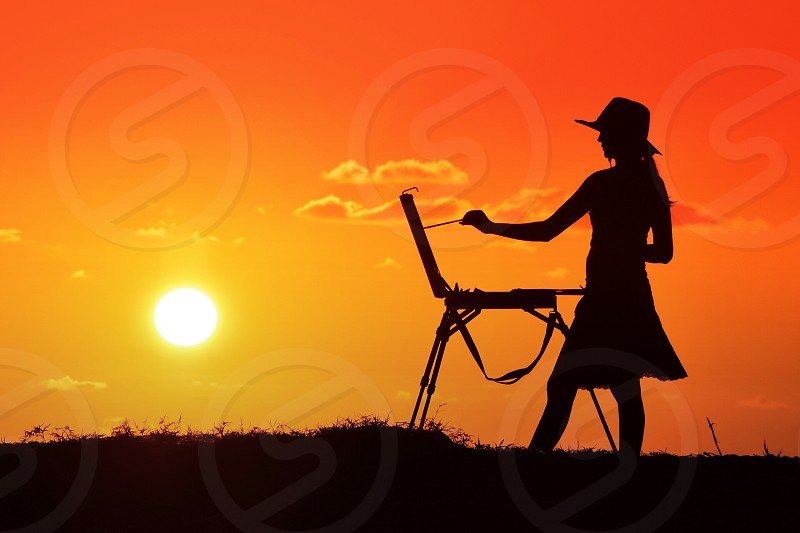 silhouette of woman painting during orange sunset photo