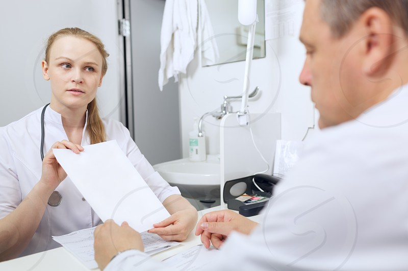 Nurse shows to the doctor blank sheet of paper photo