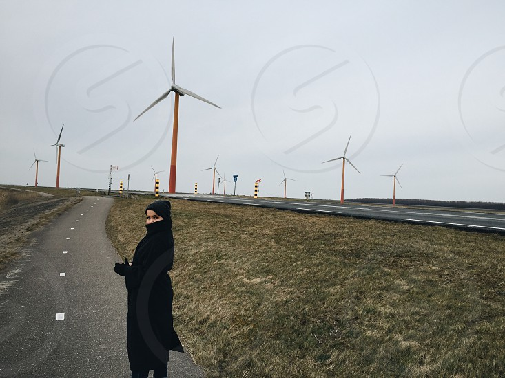 woman standing on single-lane road with wind turbines in background under grey cloudy sky during twilight photo