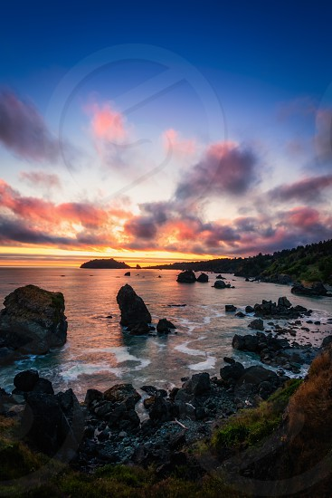 This is a color landscape photo of a vivid sunset over the Pacific Ocean. photo
